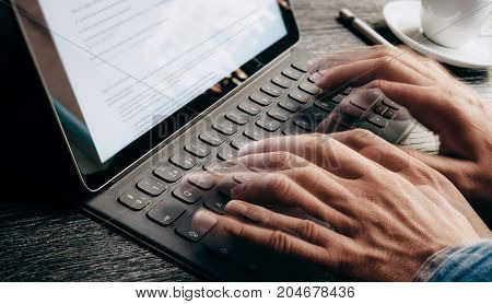 Closeup view of male hands quickly typing on electronic tablet keyboard-dock station. text information on device screen. Man working at office.Horizontal, cropped