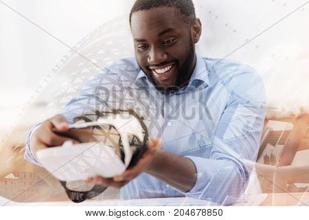 Full of advantages. Close up of surprised African American holding virtual reality mask while looking at it with surprise