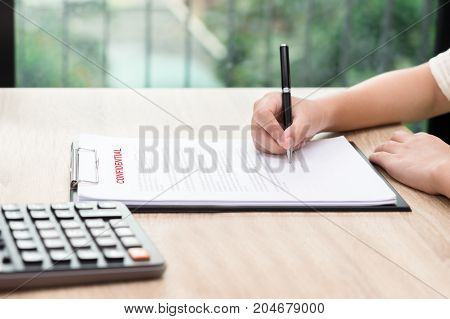 Woman signing on confidential contract with calculator on wooden desk