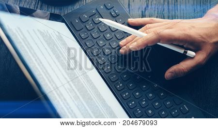 Closeup view of one male hand typing on electronic tablet keyboard-dock station. Man working at office and using electronic pen.Horizontal.Visual effects