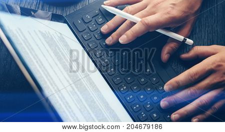 Closeup view of two male hands typing on electronic tablet keyboard-dock station. Man working at office and using electronic pen.Horizontal.Visual effects