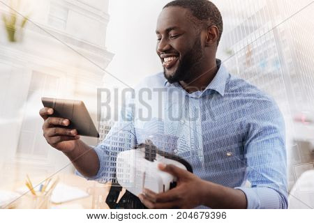 Pleasant mood. Close up of smiling African American looking at the screen while holding virtual glasses and expressing joy