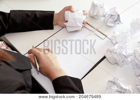 Hands of business woman crumple papers at the desk mistake document - failure business concept