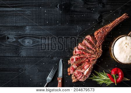Barbecue dry aged rib of beef with spice, vegetables and a glass of light beer close-up on black wooden background. Top view. Copy space. Still life. Flat lay