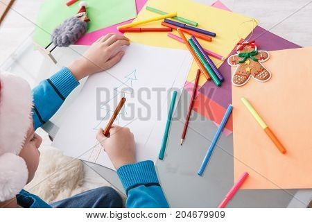 Writing letter to santa. Child in santa hats make wish list of presents for christmas. Winter holidays. Boy drawing, top view