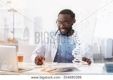 Exciting job. Busy pleasant doctor sitting at the table and expressing interest while working with notes