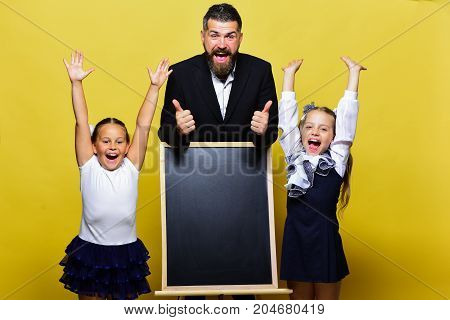 Girls And Man With Happy Faces. Schoolgirls Near Chalkboard
