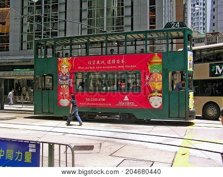 Central District, Hong Kong - March 25, 2003: A double-storey-tram runs through a street in Hong Kong, Central District.