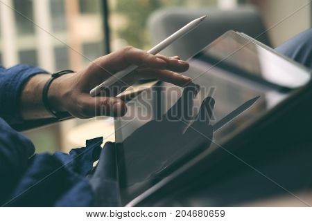Closeup view of businessman using stylus pen for working on digital tablet screen.Blurred background. Horizontal