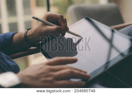 Close-up view of businessman using stylus pen for working at office on digital tablet screen.Blurred background. Horizontal