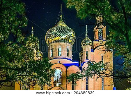 The Church of THE HOLY APOSTLES AND THE GOSPEL JOHN OF BOGHOSLOV in green park at night. Pokrov town, Ukraine, 2017