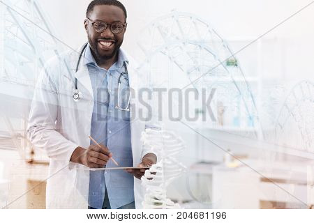 Appropriate medical care. Waist up of kind hearted positive doctor standing in front of you and smiling