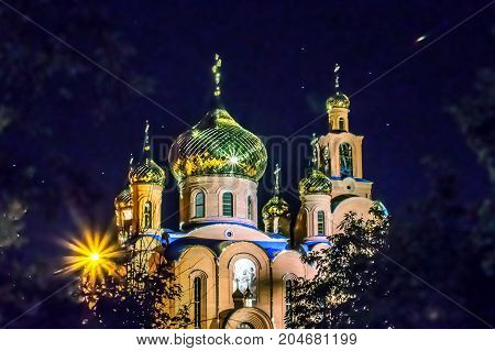 The Illuminated Church of THE HOLY APOSTLES AND THE GOSPEL JOHN OF BOGHOSLOV at night. Pokrov town, Ukraine, 2017