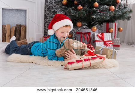 Cute happy boy in santa hat hug toy rabbit, christmas present on holiday morning in beautiful room. Male child got Xmas gift, lying near decorated fir tree and fireplace. Winter holidays concept