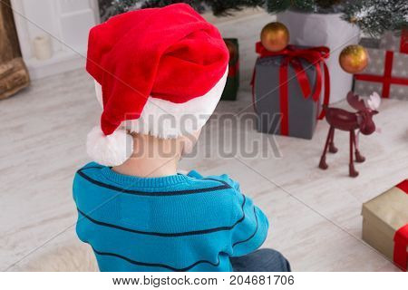 Cute happy boy in santa hat unwrap christmas present box on holiday morning in beautiful room interior. Male child sitting with his back to camera, closeup. Winter holidays concept