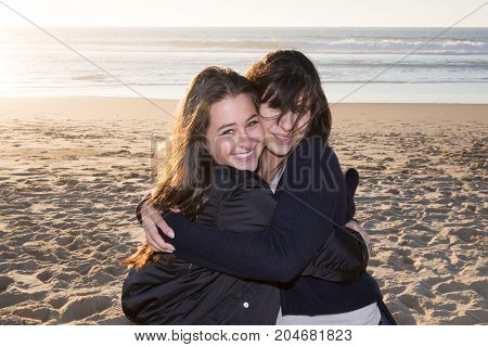 Mature Mother With Her Teenage Daughter Looking In One Direction On Beach Backlit With Sun