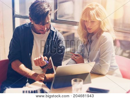 Two young coworkers working on laptop computer at sunny office.Woman holding paper documents and pointing on notebook screen. Horizontal.Blurred background.Cropped.