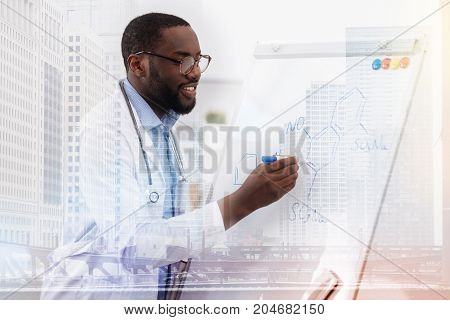 Development of science. Positive concentrated doctor writing down chemical formula while using a board and expressing curiosity