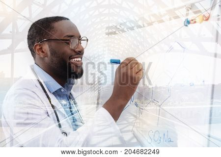 Constantly diligent. Close up of talented successful researcher standing at the board and creating new chemical formula while writing it down