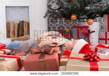 Happy girl child in santa hat lay on warm carpet among Christmas gift boxes. Xmas holiday concept. Side view of excited cute kid got lots of presents