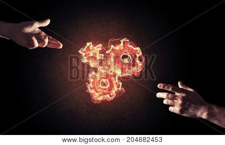 Hand of businessman presenting fire gear mechanism on dark background