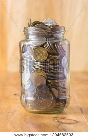Glass jar full of coin on the table