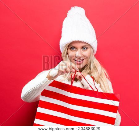 Happy young woman holding a shopping bag on a solid background