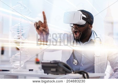 Amazing reality. Close up of surprised African American doctor looking through virtual glasses and putting forward his finger while being surprised