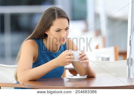 Single angry woman thinking and holding a cup sitting in a bar terrace