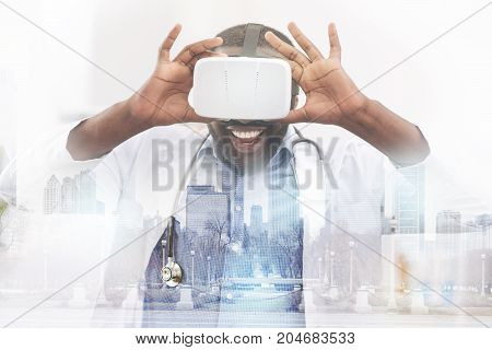 Incredible emotions. Close up of pleasant African American doctor wearing virtual glasses and touching them while expressing delight