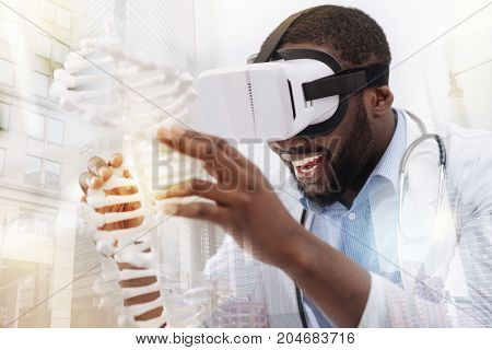 Exciting day. Close up of young delighted doctor using virtual glasses while looking at genome model and smiling