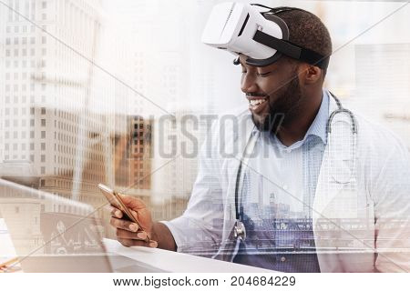 Little break. Smiling handsome doctor using a mobile phone while sitting at the table with a mask on his head