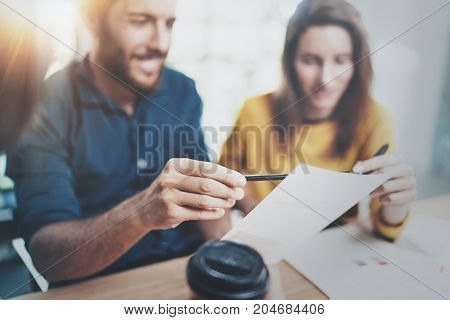 Teamwork process concept.Coworkers working at office.Closeup view of male hand pointing on paper document. Horizontal.Blurred background.Selective focus