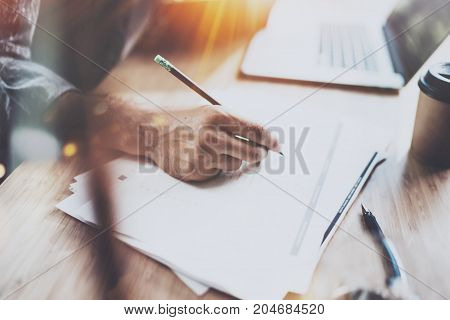 Businessman working at office.Closeup view of male hand making notes on paper document. Horizontal.Blurred background