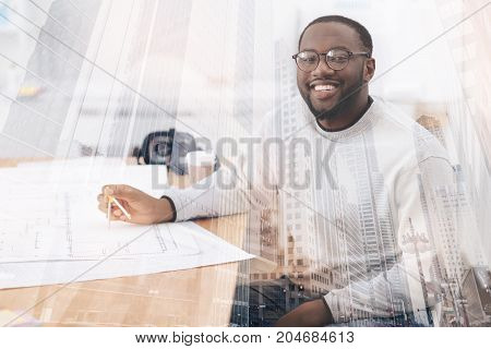 Pleased with work. Young educated African American sitting at the table while using compasses and smiling at you