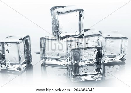 Transparent ice cube with reflection and water drops on white background. Closeup of cold crystal blocks group cutout