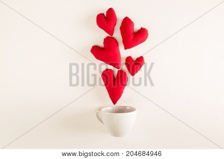 Handmade heart cushions with coffee cups on a white background