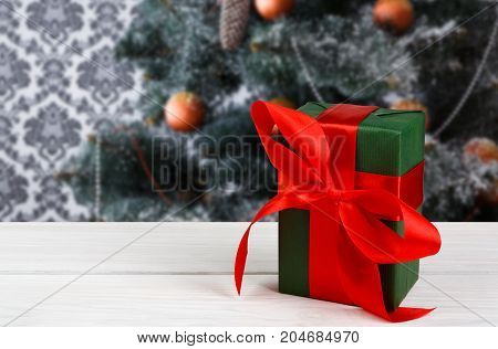 Christmas present decorated with red ribbon on table, closeup, selective focus. Christmas tree background.