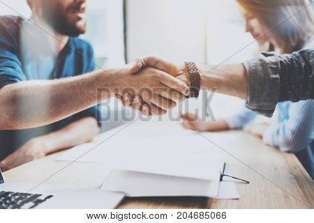 Closeup view of Business male partnership handshake.Photo two coworkers handshaking process.Successful deal after great meeting.Horizontal, blurred background