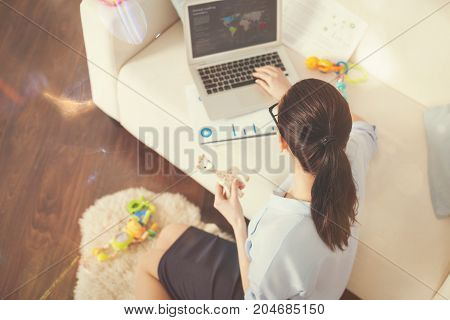 Have a look. Single mother holding toy in left hand leaning on sofa while working at project at home