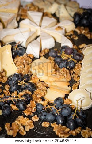 Cheese platter with different cheese, walnuts and grapes on a table at a festive event