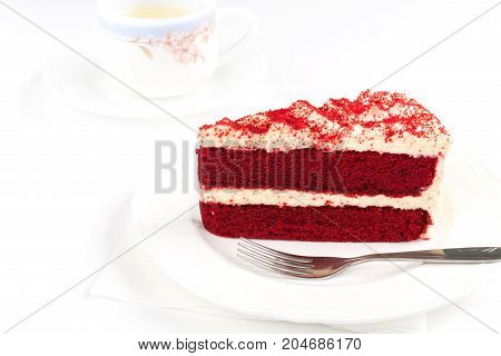 Red Velvet Cake sliced in piece on white plate with stainless fork on white background with cup of green tea for celebrate X'mas season occasion Valentines day birthday or special holiday events
