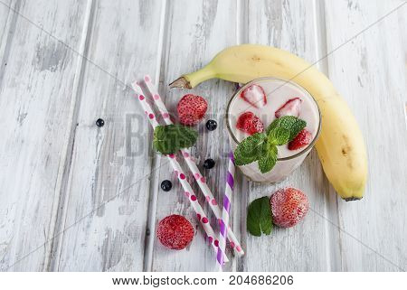 Berry Smoothies Of Strawberries, Banana  In Glasses And Ingredients On A Wooden Table