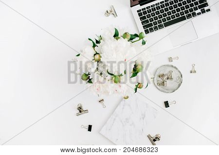 Flat lay home office desk. Woman workspace with laptop white peony flowers bouquet accessories marble diary on white background. Top view feminine background.