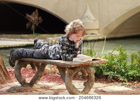 San Antonio, Texas - February 20, 2011: Cute kid boy reading a book on the bench on Riverwalk in San Antonio, Texas.
