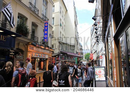 PARIS, FRANCE - JUNE 5, 2017: People wondering around Latin Quarter. Street scene with shops, cafes and restaurants with locals and tourists walking in one of the most famous parts of french capital.