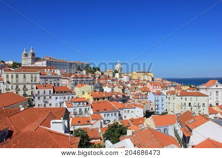 Famous portuguese red roofs in Alfama old town historical district on summer time. Miradouro Portas do Sol viewpoint in Lisbon Portugal. Empty clear blue sky and cityscape architecture background