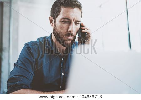Young businessman using smartphone at office and making notes.Blurred background.Horizontal.Cropped