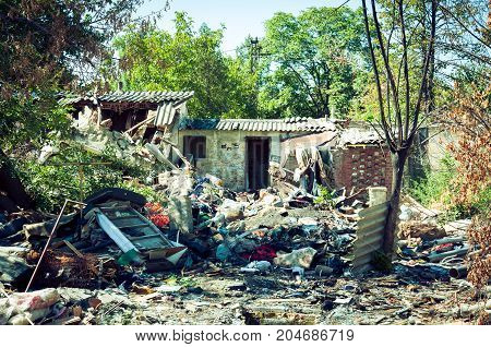 Abandoned ruin of house after grenade explosion in bombing with remains all over the yard. War zone.