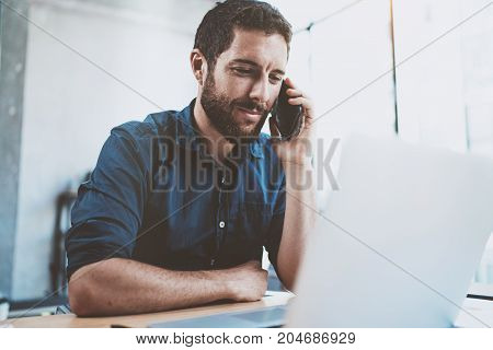Smiling businessman using smartphone at office and making notes.Blurred background.Horizontal
